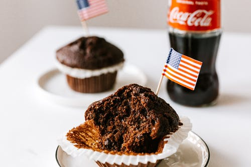 Sweet cakes with toothpick american flags placed on table with soda bottle