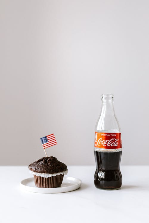 Muffin with miniature US flag and coke bottle placed on white table