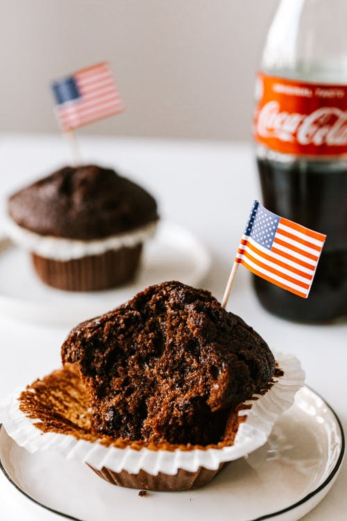 Sweet muffins with miniature american flags placed on table with coke bottle