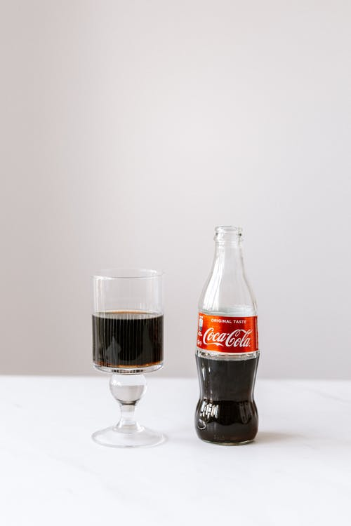 Glass of cola poured from bottle