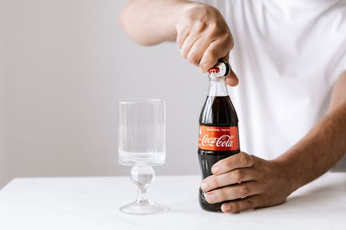 Crop man opening glass bottle of cola