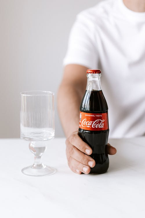 Crop faceless young male in white t shirt holding bottle of refreshing coke while sitting at table with glass