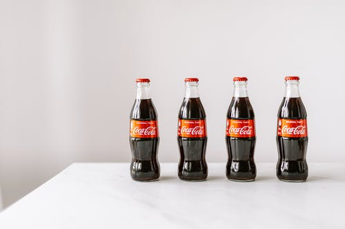 Glass bottles of cola on white table