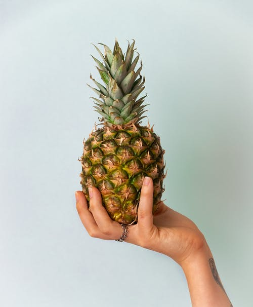 Person Holding Pineapple Fruit Near White Wall