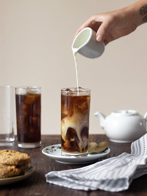 Crop person pouring cream into iced coffee for breakfast