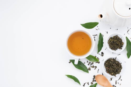 Top view of cup of hot tea near spilled dry green brew and fresh leaves with ceramic teapot