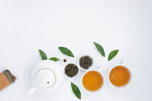 Green tea with brew on white table