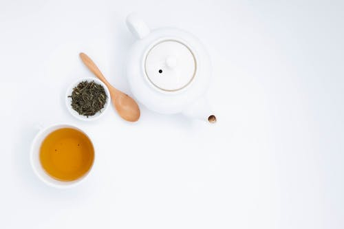 Top view of cup with hot drink near green tea brew with wooden spoon and ceramic teapot