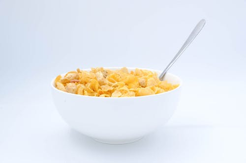 Bowl with cornflakes and spoon on white background