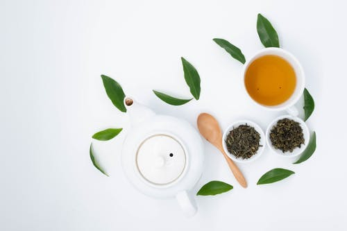 From above of cup with green tea near dry and fresh leaves with ceramic teapot on white table