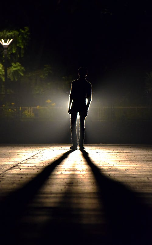 Unrecognizable man on shining wooden walkway illuminated by street light