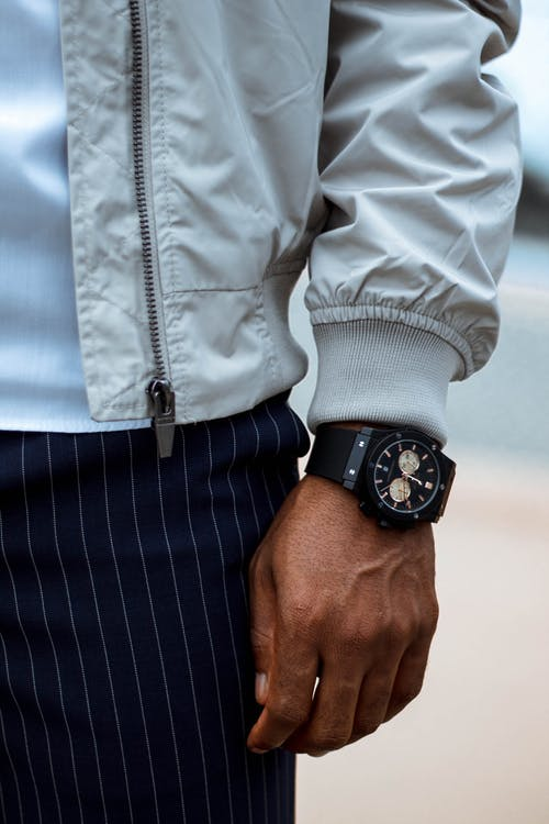 Crop man in stylish wear and wristwatch outdoors