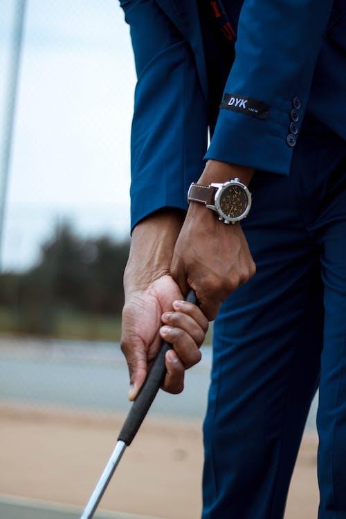 Crop stylish businessman in luxury wristwatch playing golf using stick