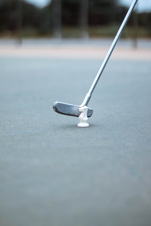 White and Gray Golf Club on Gray Surface