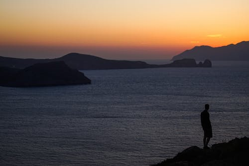 Silhouette of anonymous man on mount near ocean at sunset