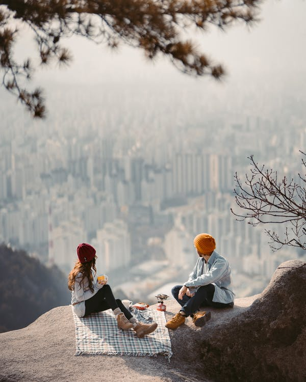 A Couple Sitting on Cliff Having a Picnic
