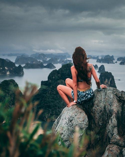 Woman in Blue and White Bikini Sitting on Rock Near Sea