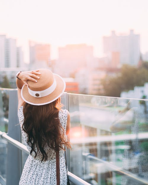 Woman in White and Black Floral Long Sleeve Shirt Wearing Brown Fedora Hat