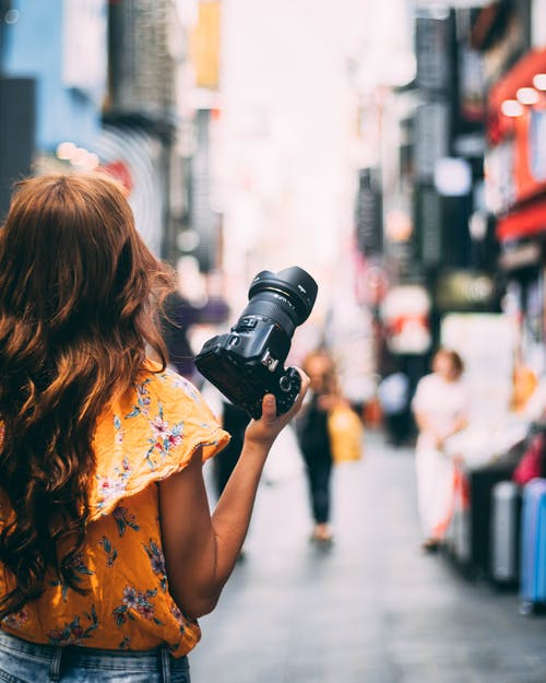 Woman in Yellow Floral Dress Holding Black Dslr Camera