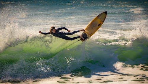 Full body of male surfer in wetsuit riding surfboard on foamy sea waves in summer day