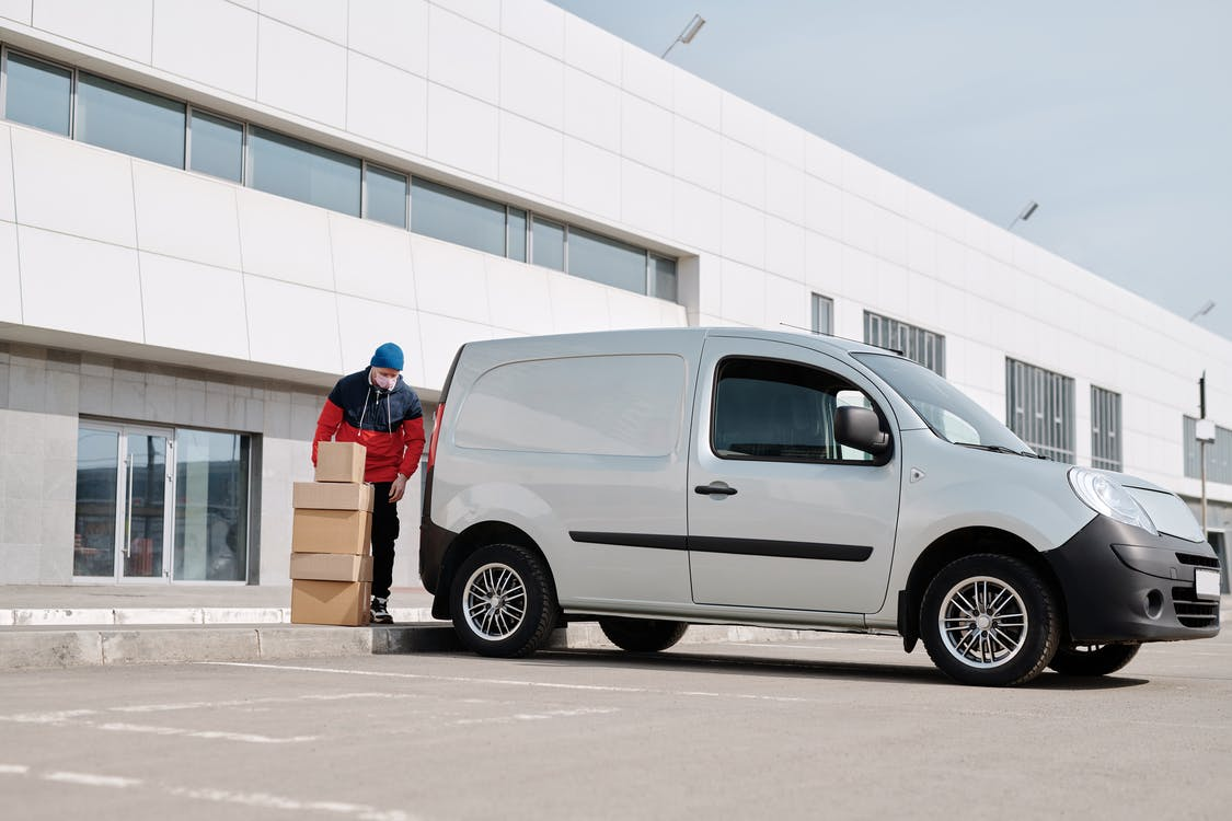 Delivery Man With Boxes next to a White Van