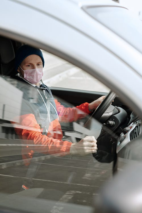 Man Wearing a Face Mask Driving a Vehicle