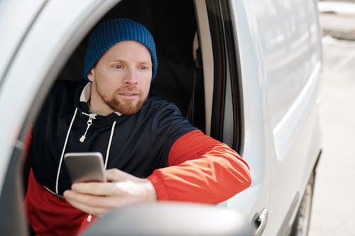 Man in Red and Black Hoodie Wearing Blue Knit Cap Holding Silver Iphone 6