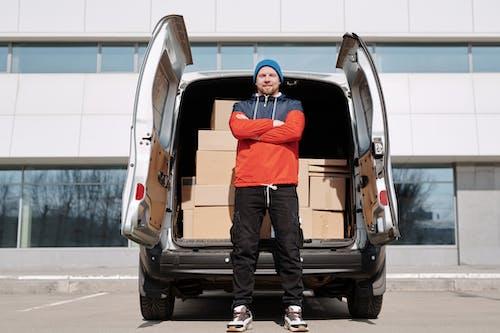 Man in Red and Black Jacket and Brown Pants Standing Beside Brown Van