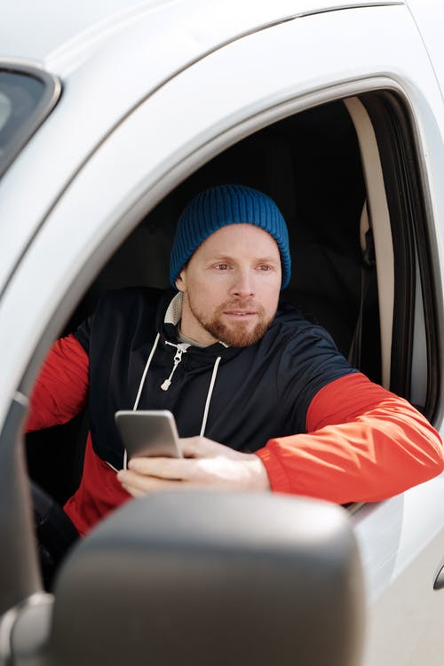 Man in Red and Black Jacket Wearing Blue Knit Cap Holding Silver Ipad