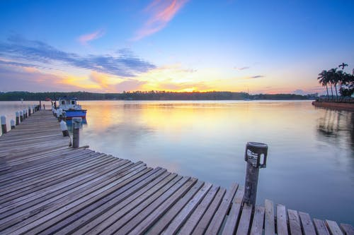 Sunset sky over calm sea with wooden pier