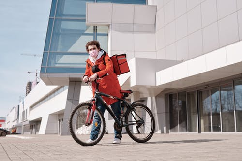 Delivery Man Wearing a Face Mask and Holding a Bicycle