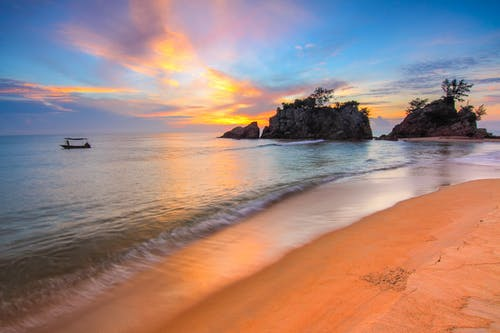 Amazing scenery of rocky formations in ocean waving near empty sandy beach against cloudy sunset sky