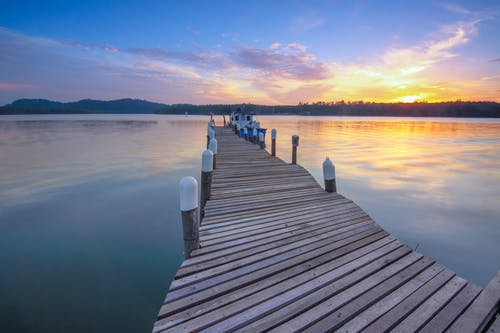 High angle of empty wooden dock leading along peaceful sea against cloudy sunset sky
