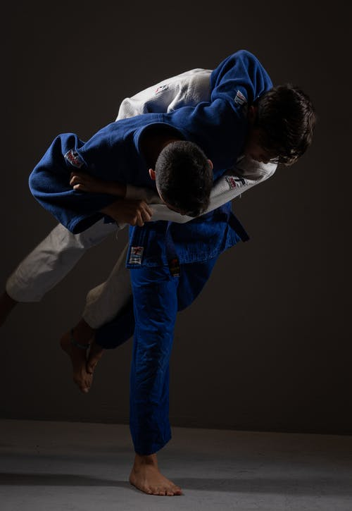 Anonymous strong sportsmen practicing judo on floor