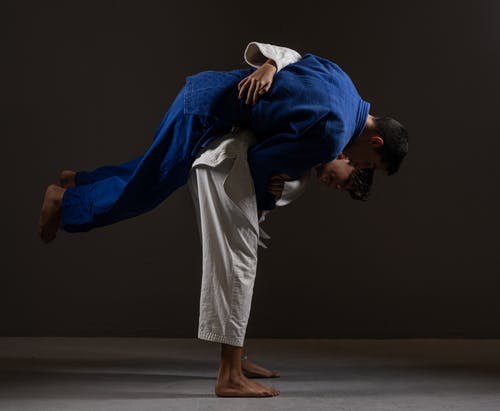 Side view of young barefooted Asian male judokas in uniform fighting on floor against black background