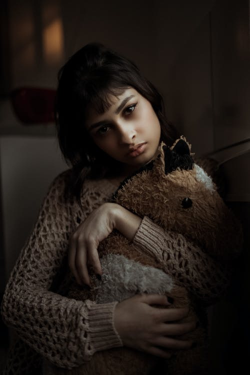Calm young ethnic lady hugging soft toy horse