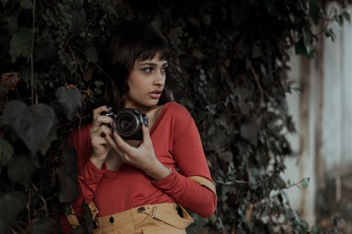 Stylish young ethnic female tourist photographing on camera on street