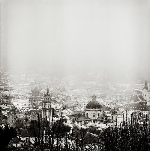 From above of black and white ancient cathedral and tower in city covered in snow against overcast foggy sky