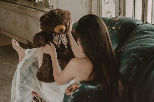 Woman in White Tank Top Holding Brown Bear Plush Toy