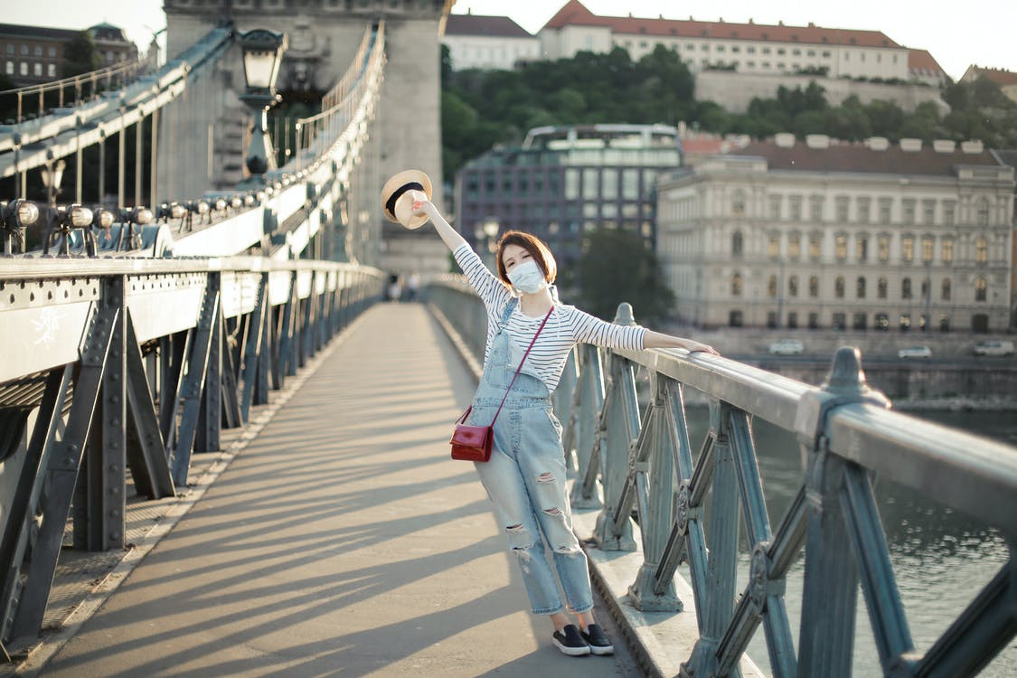 Full body of anonymous happy young female traveler in stylish outfit and face mask standing on bridge crossing river with outstretched arm in ancient city