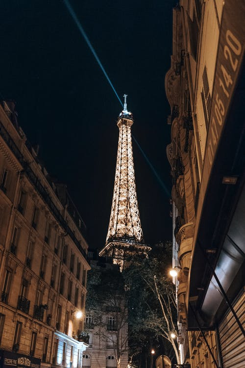 Illuminated Eiffel Tower between aged buildings in evening