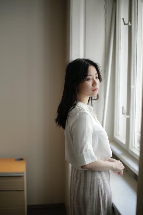 Pensive young ethnic woman standing near window on sunny day