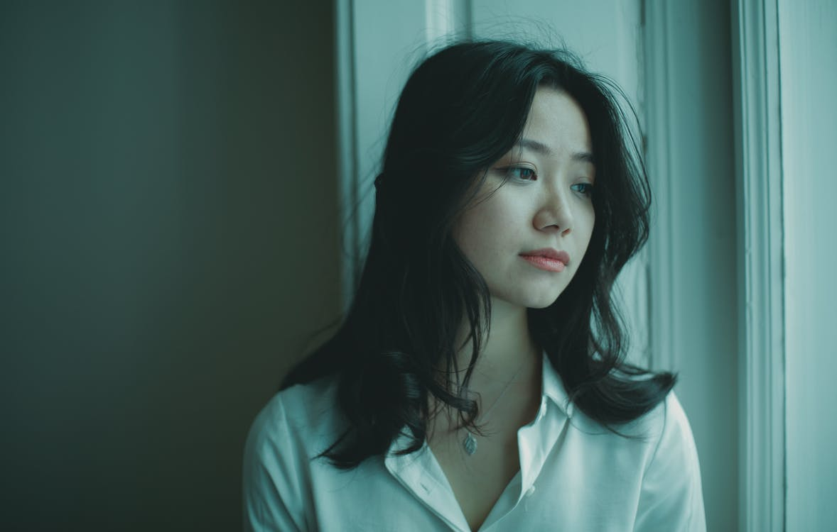 Upset young ethnic lady with long dark hair sitting on windowsill and looking away thoughtfully