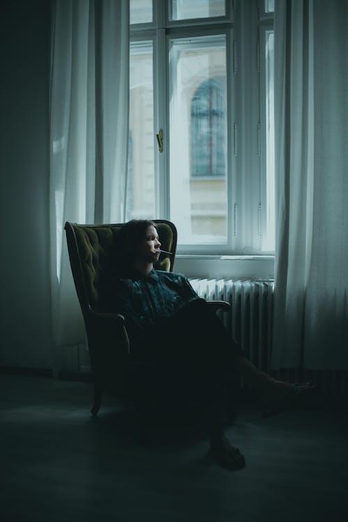 Pensive person resting in armchair in dark living room