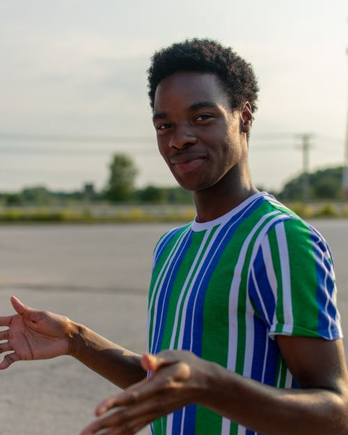 Happy black man showing gesture with hands on street
