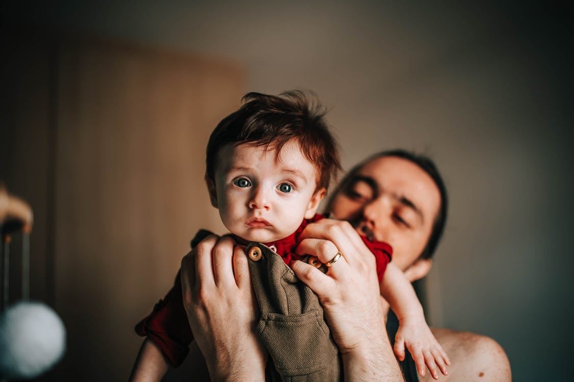 Happy young bearded father holding adorable baby boy in hands in light room