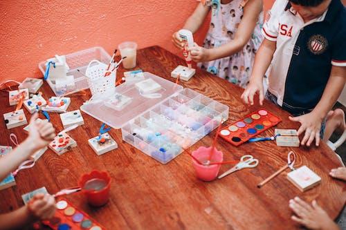Crop creative children painting with gouache in kindergarten