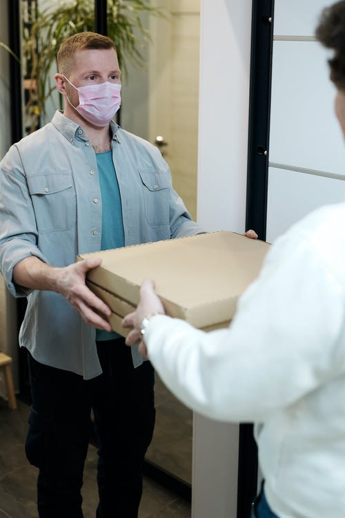 Man Wearing a Face Mask Receiving a Pizza Delivery