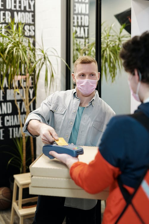 Man Wearing a Face Mask Paying for Pizza Delivery