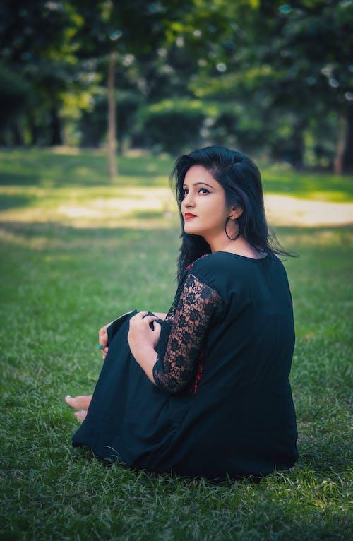 Woman in Black Long Sleeve Dress Sitting on Green Grass Field